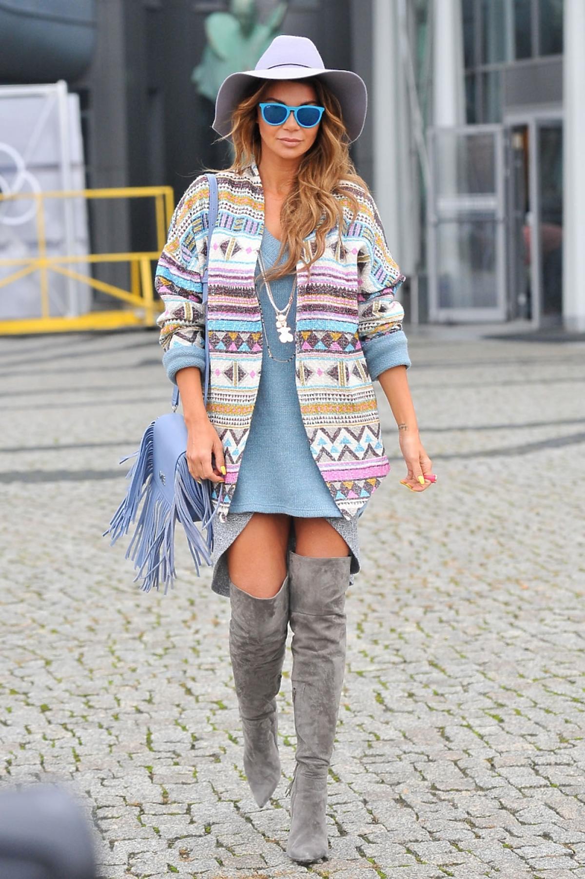 Edyta Górniak w swetrze w kolorowe printy, niebieskim swetrze, szarych kozakach, fioletowym kapeluszu, niebieską torbą z frędzlami