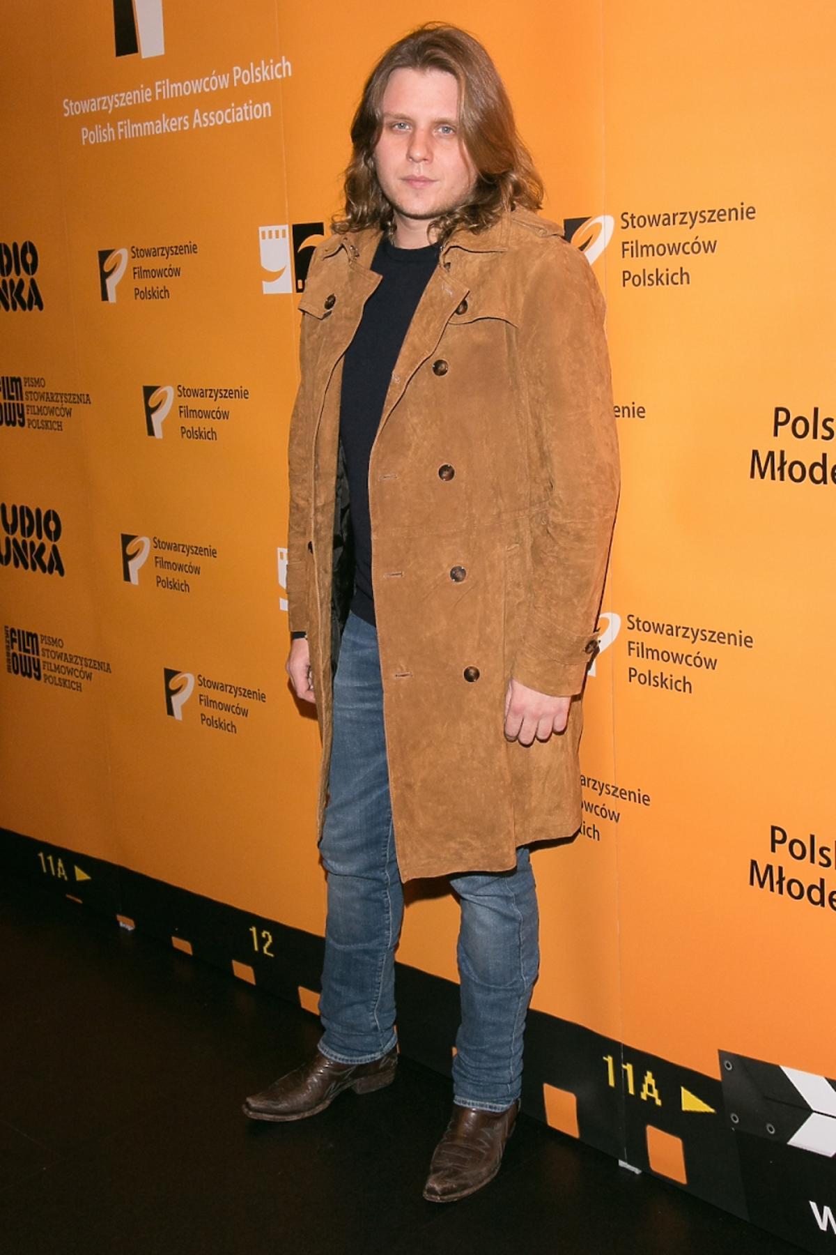 Piotr Woźniak Starak w brązowym płaszczu