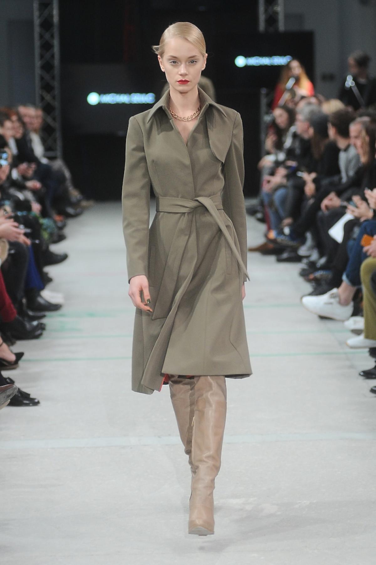 Modelka z pokazu Michała Szulca w sukience w kolorze khaki, beżowych kozakach