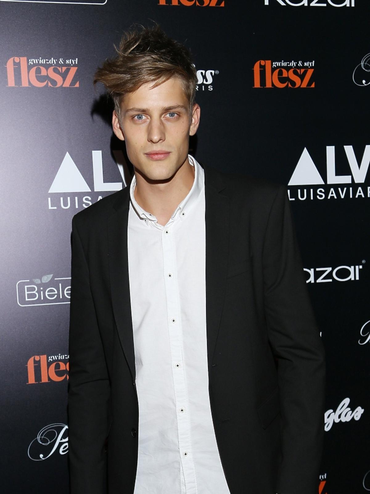 Jakob Kosel w czarnej marynarce, białej koszuli i dżinsach