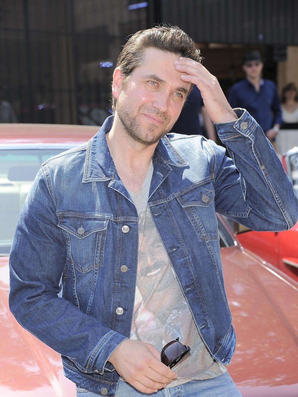Marcin Dorociński w kurtce jeansowej oparty o maskę samochodu