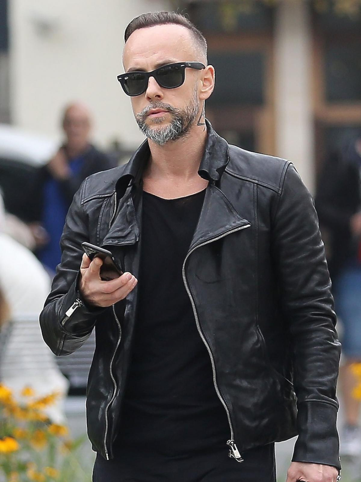 Nergal na ulicy w czarnej skórzanej kurtce, okularach przeciwsłonecznych trzyma w ręku telefon komórkowy