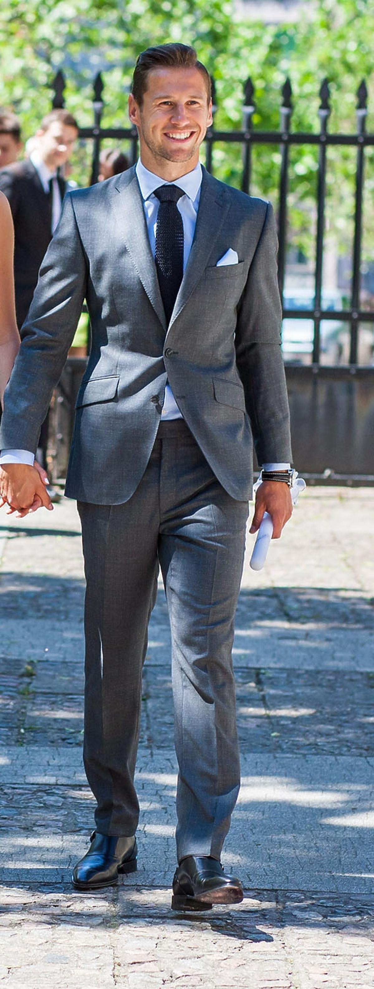 Uśmiechniety Grzegorz Krychowiak w eleganckim jasnym garniturze i krawacie