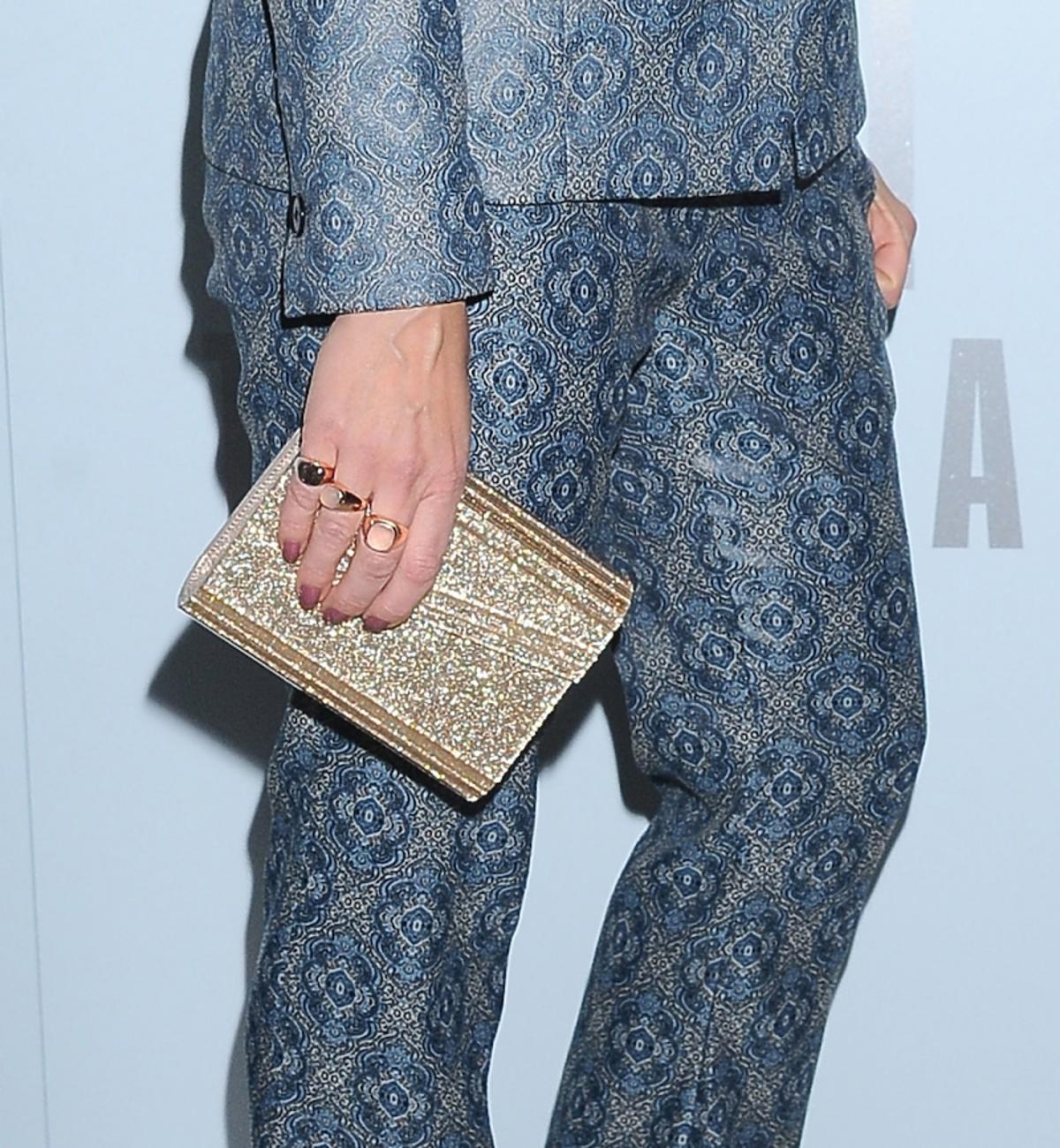 Kinga Rusin w niebieskim garniturze w printy, ze złotą małą torebką