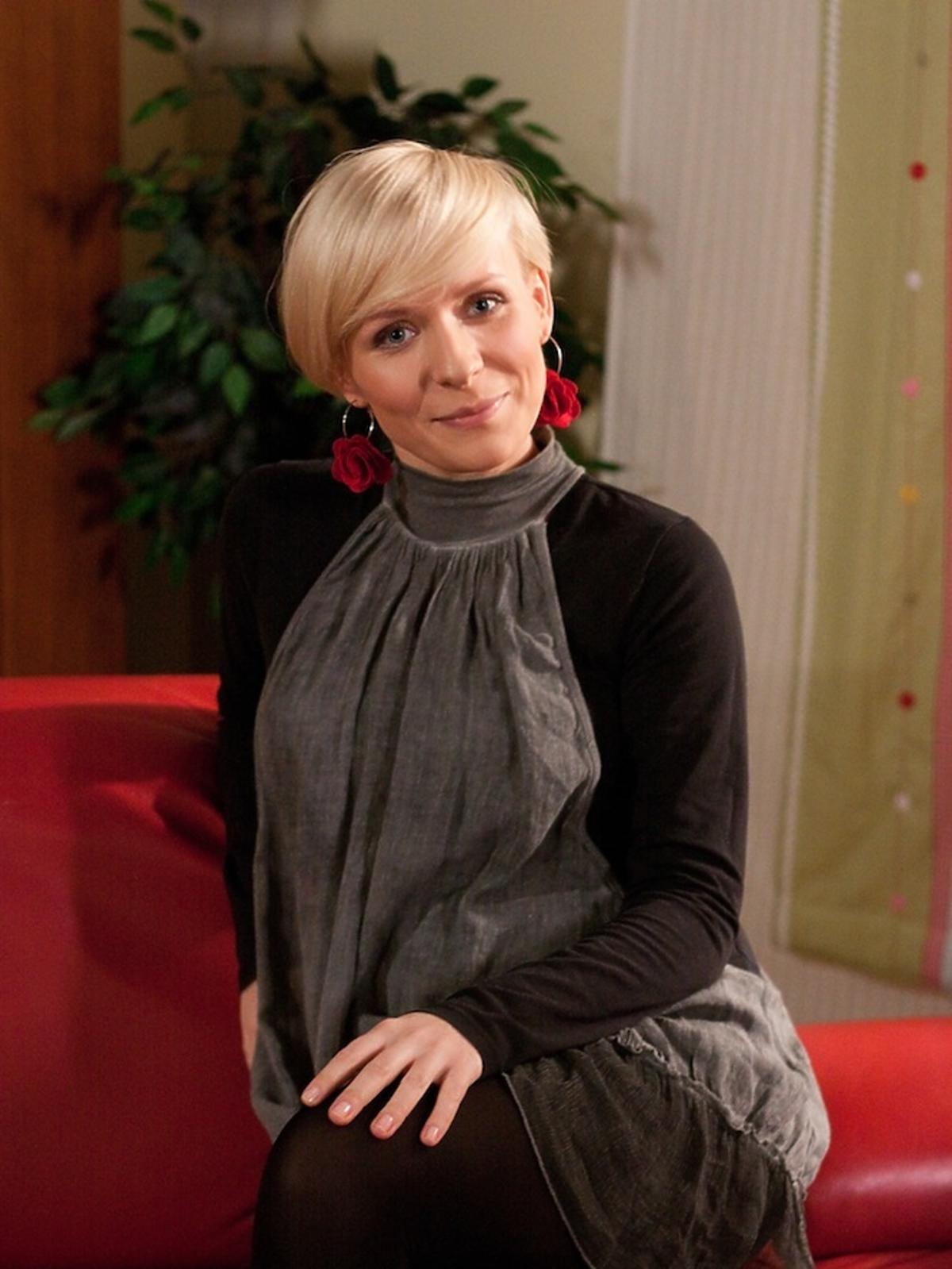 Aneta Zając na czerwonej kanapie w krótkich włosach w serialu Pierwsza Miłość z 2010 roku