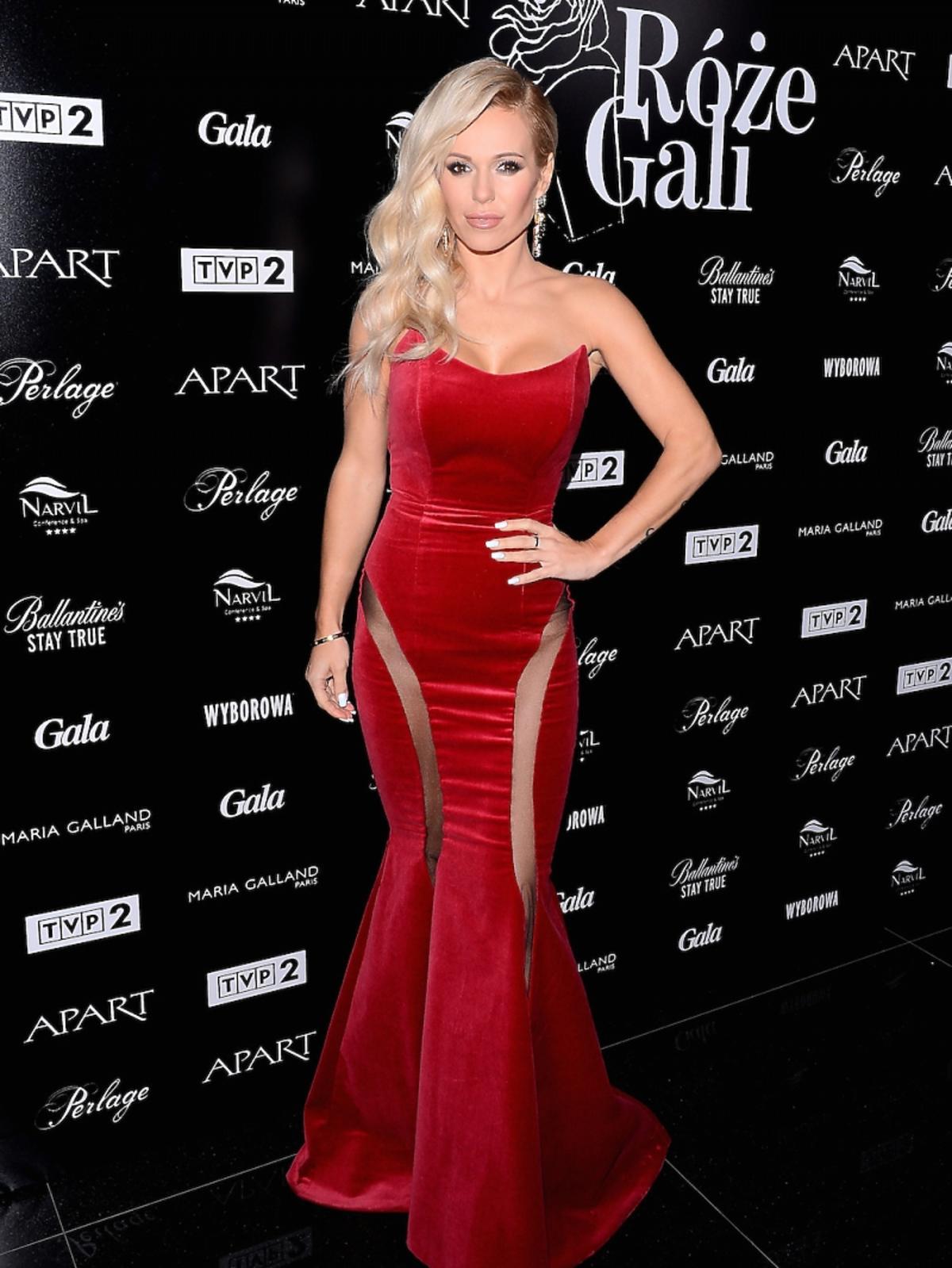 Doda w długiej czerwonej sukience na czerwonym dywanie