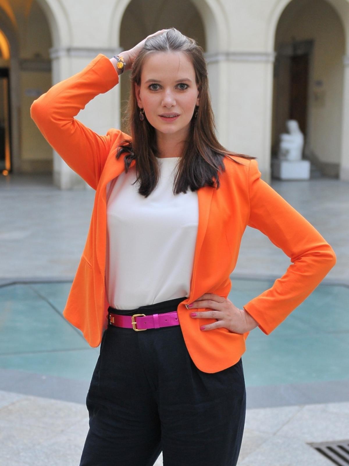 Karolina Malinowska w czarnych spodniach i pomarańczowej marynarce