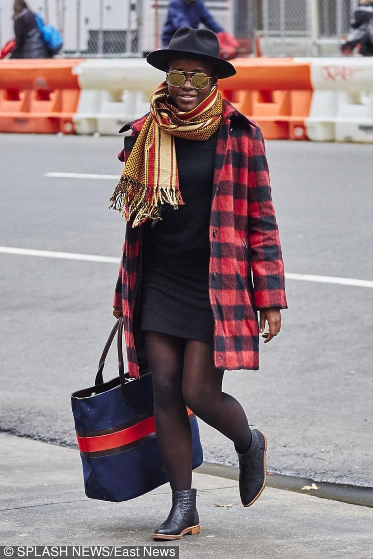 Lupita Nyong'o w czarnej sukience i kapeluszu, czerwony czarnym płaszczu w kratę , kolorowym szalu z duża torbą