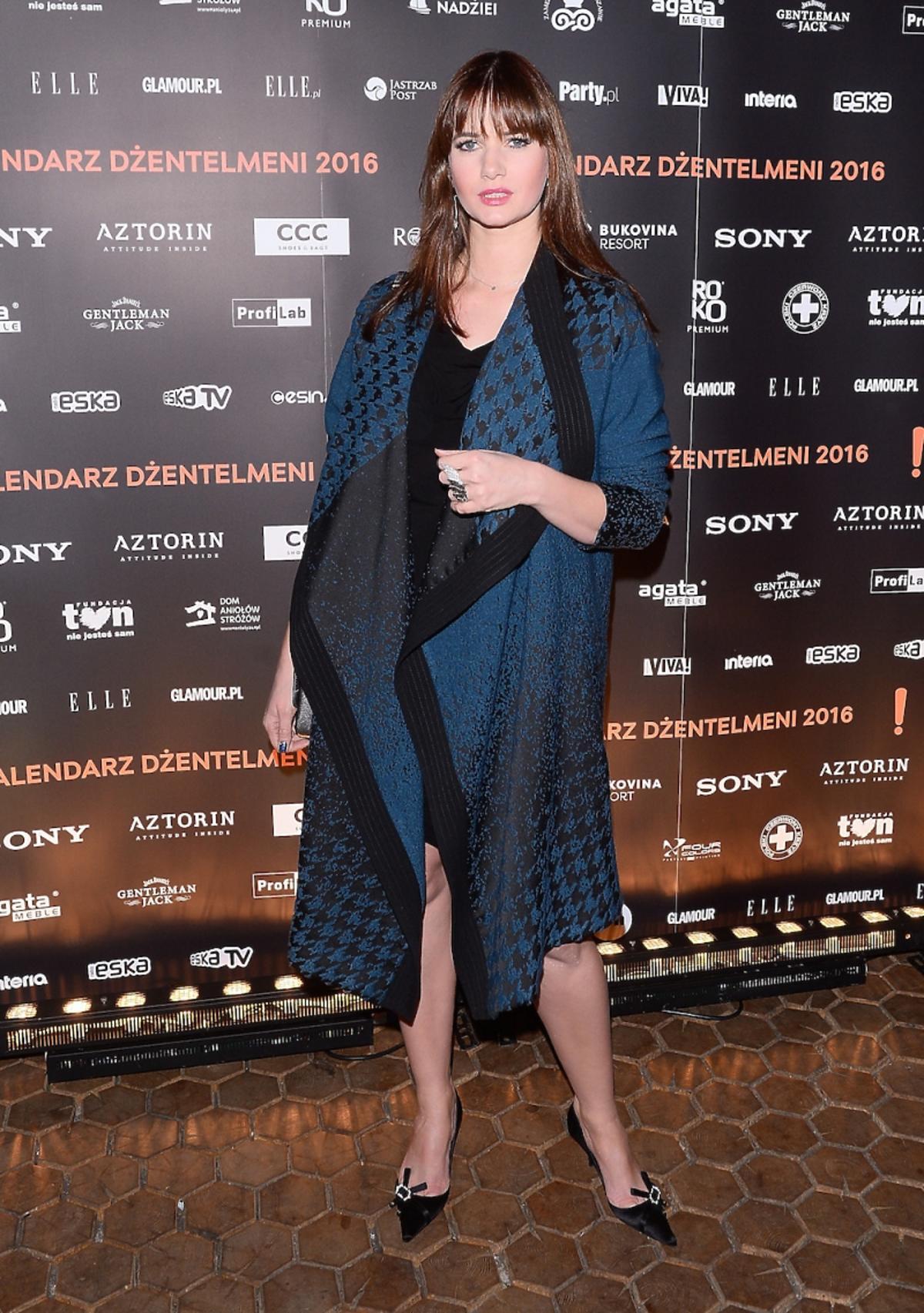Karolina Malinowska w niebieskim płaszczu w pepitkę, czarnej sukience i butach