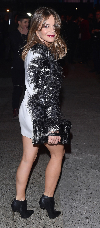 Edyta Herbuś w białej sukience z piórami na rękawie, w czarnych botkach z błyszczącą torebką do ręki