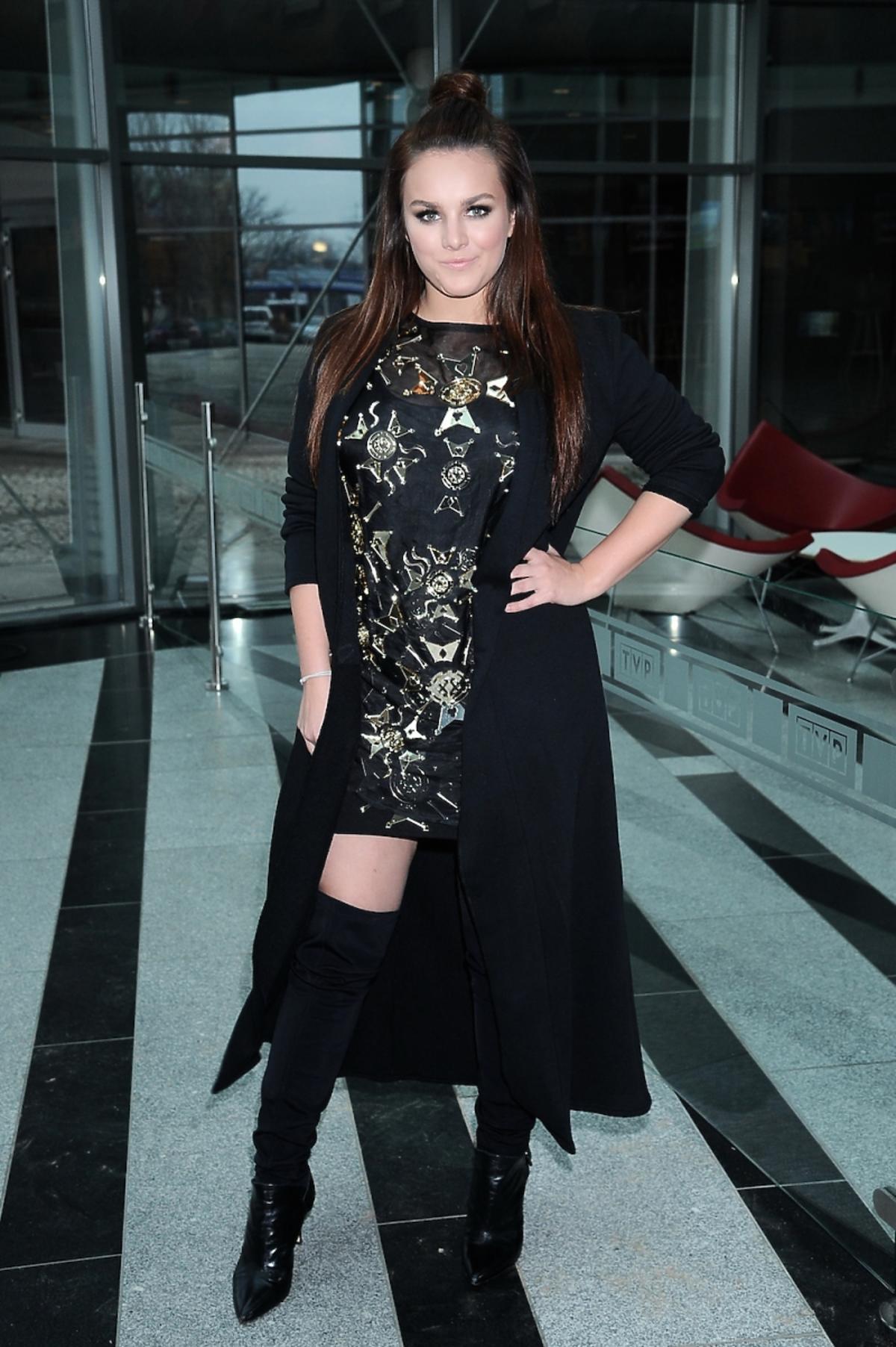 Ewa Farna w czarnym płaszczu i botkach, sukience z metalowymi ozdobami