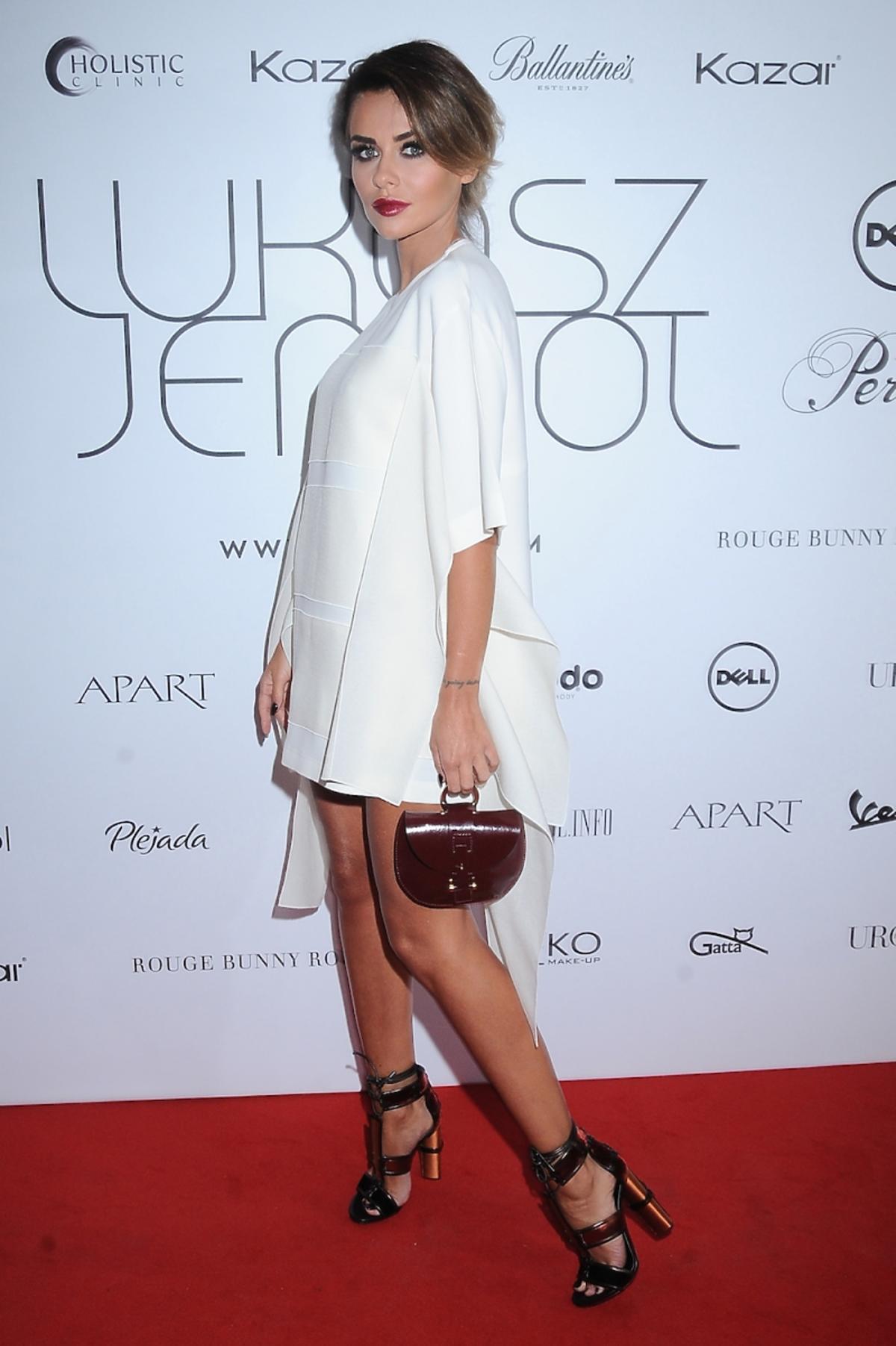 Natali Siwiec w białej sukience z wiśniową małą torbą