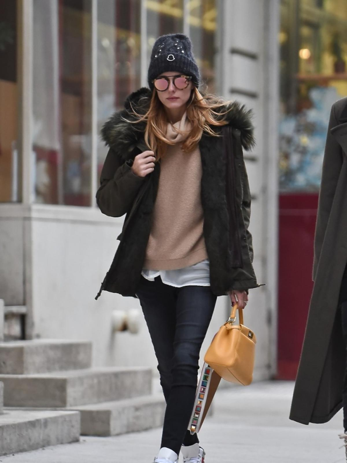 Olivia Palermo czarnych spodniach i parce, czapce, beżowym swetrze