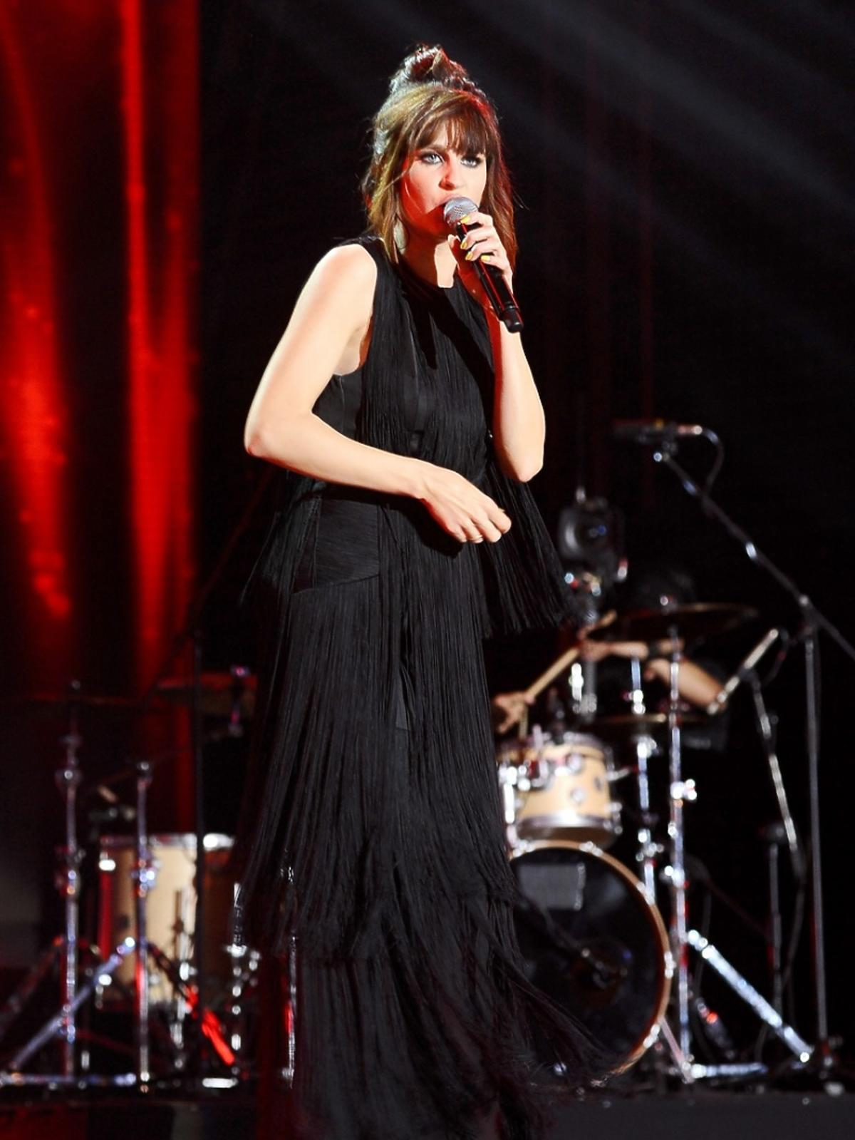 Sylwia Grzeszczak w czarnej długiej sukience, stoi na scenie z mikrofonem