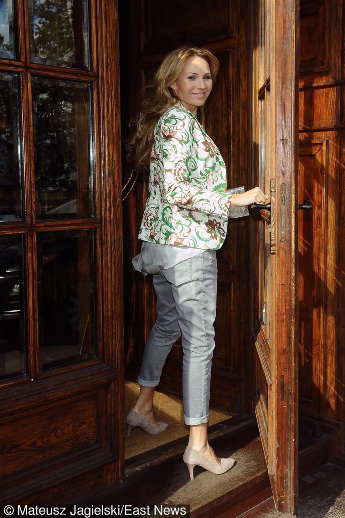 Anna Guzik wchodzi przez wielkie drewniane drzwi