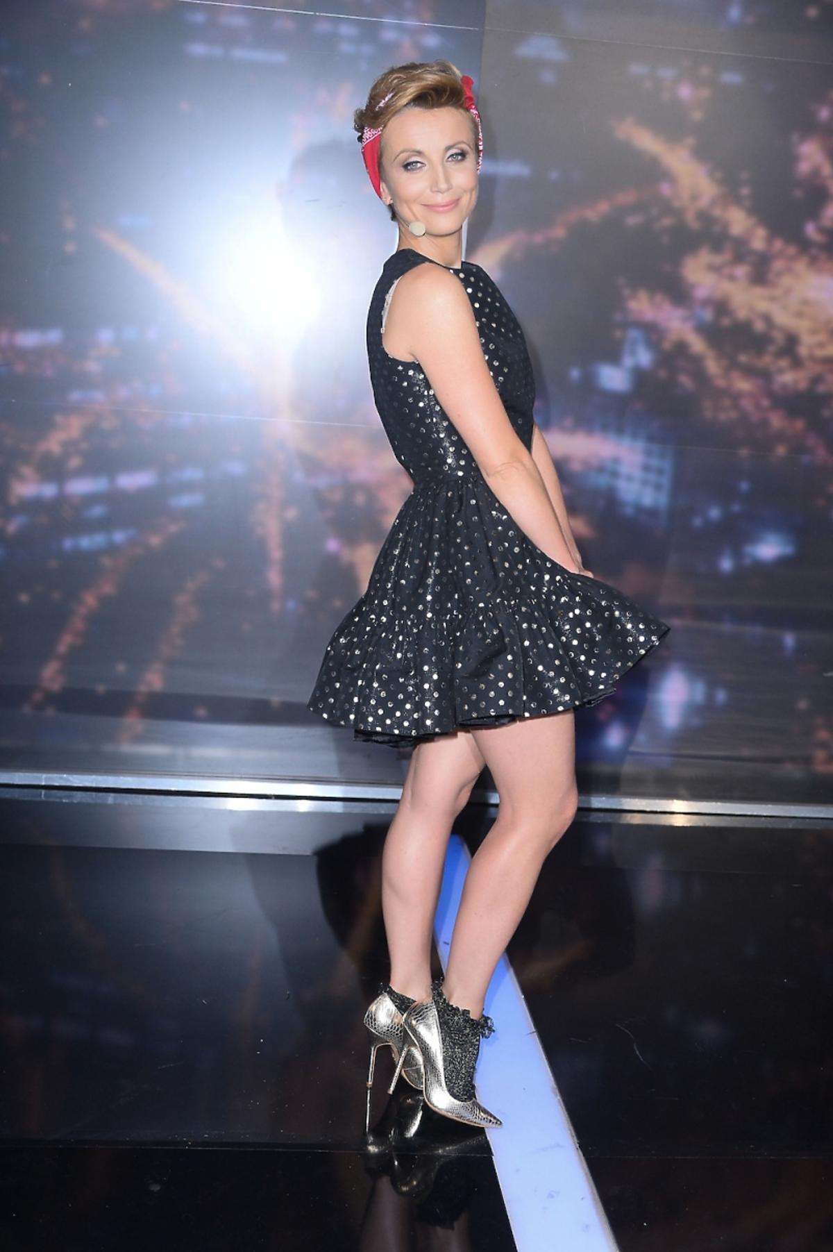 Katarzyna Zielińska w czarnej błyszczącej sukience w szpilkach i skarpetkach