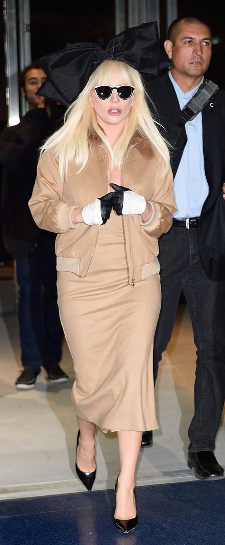 Lady gaga w kremowej sukience i kurtce bomber z czarną kokardą na głowie