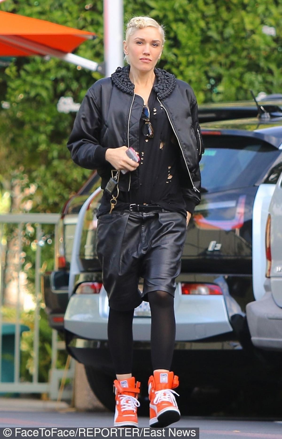 Gwen Stefani w czarnej kurtcem spodenkach, legginsach i kolorowych butach