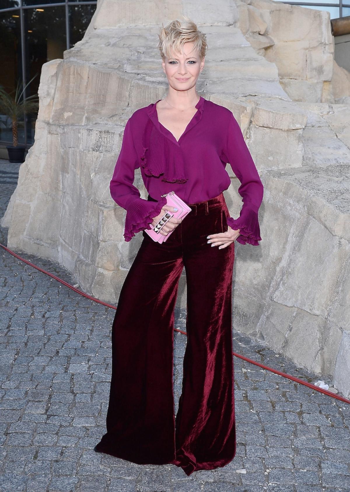 Małgorzata Kożuchowska w bordowych spodniach, fioletowej koszuli