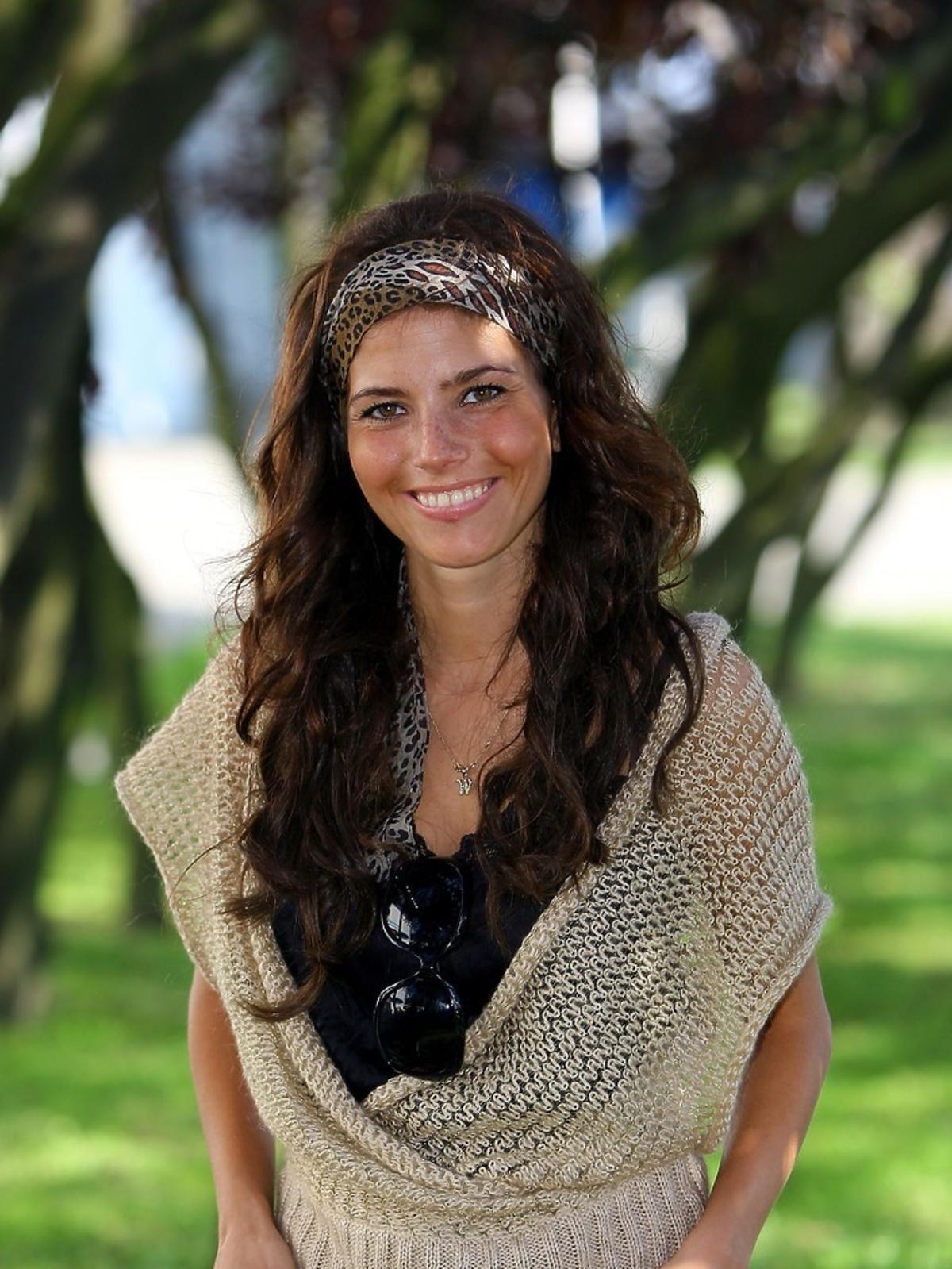 Weronika Rosati uśmiechnieta, pozuje na tle drzew