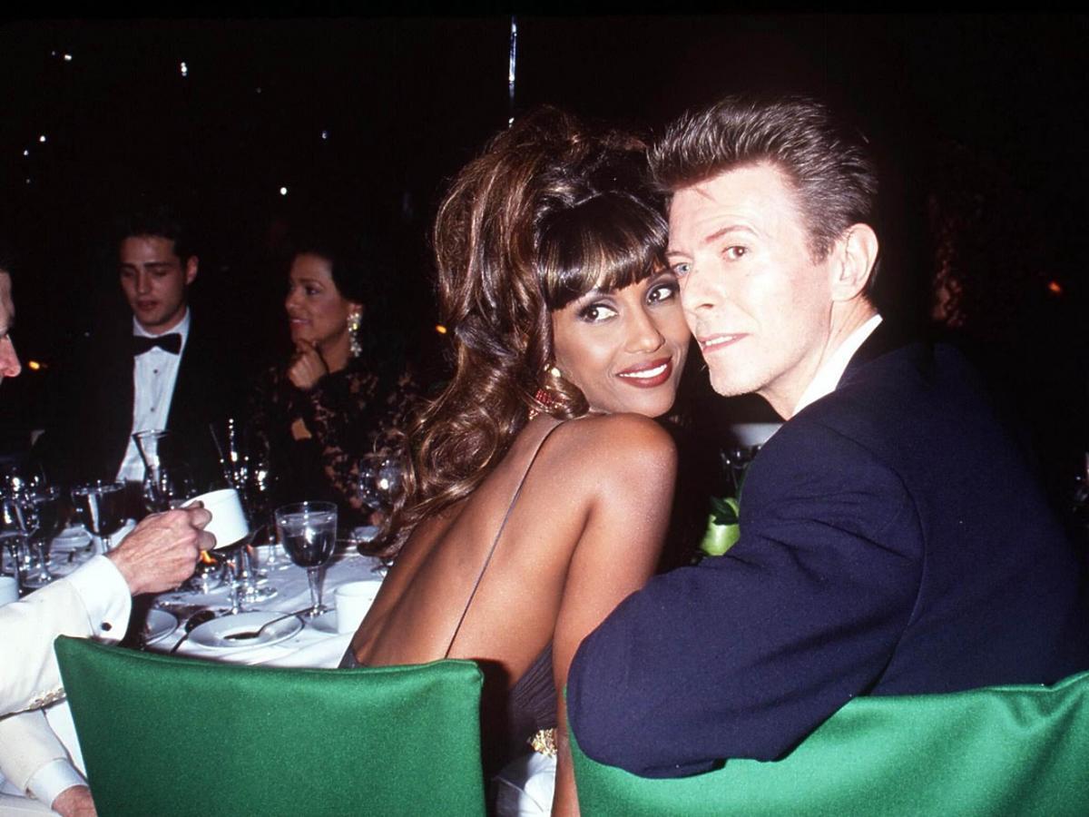 David Bowie z Iman siedzą przy stole, odwracając się i patrząc w kamerę