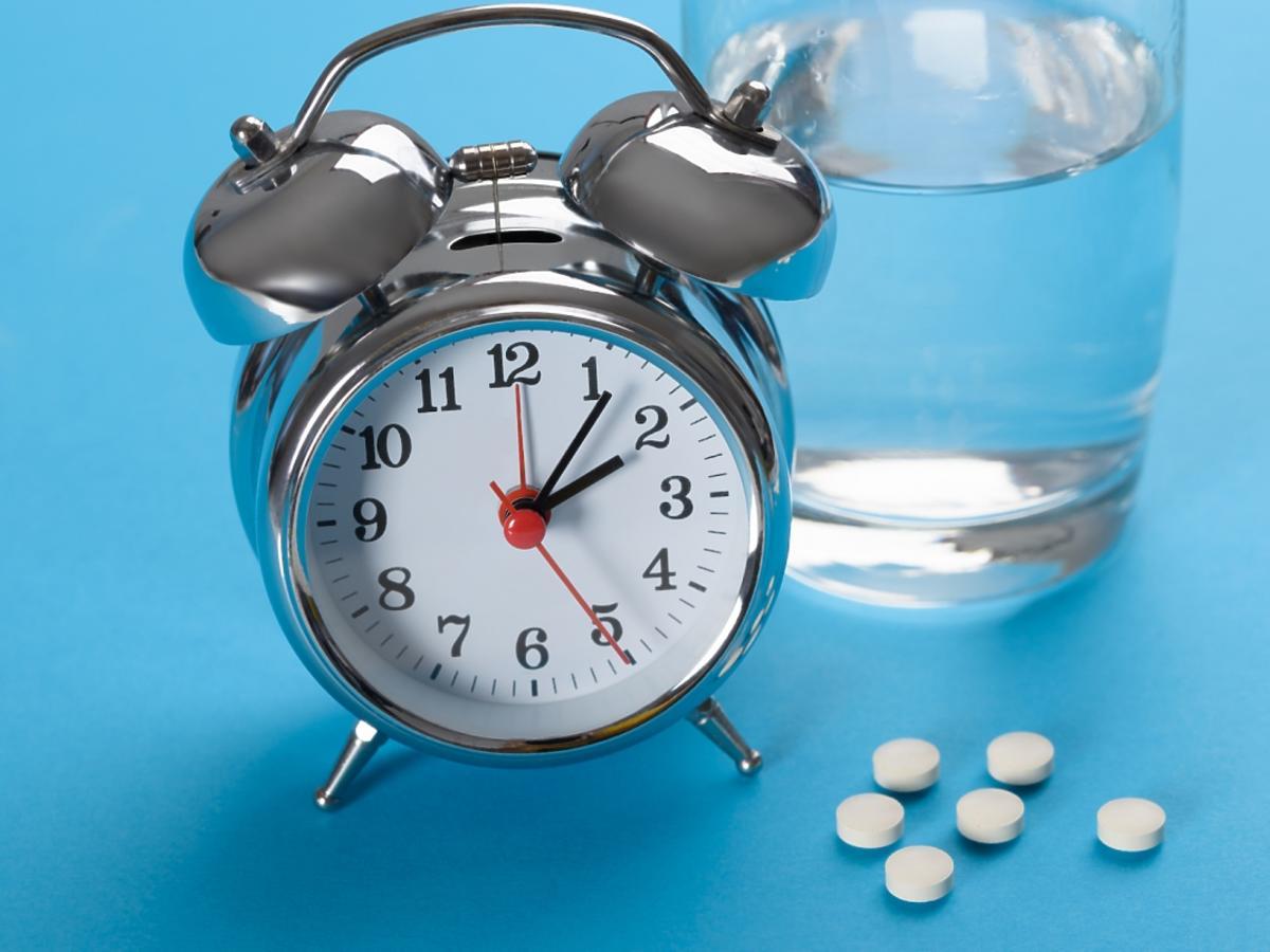 budzik, leki i szklanka z wodą