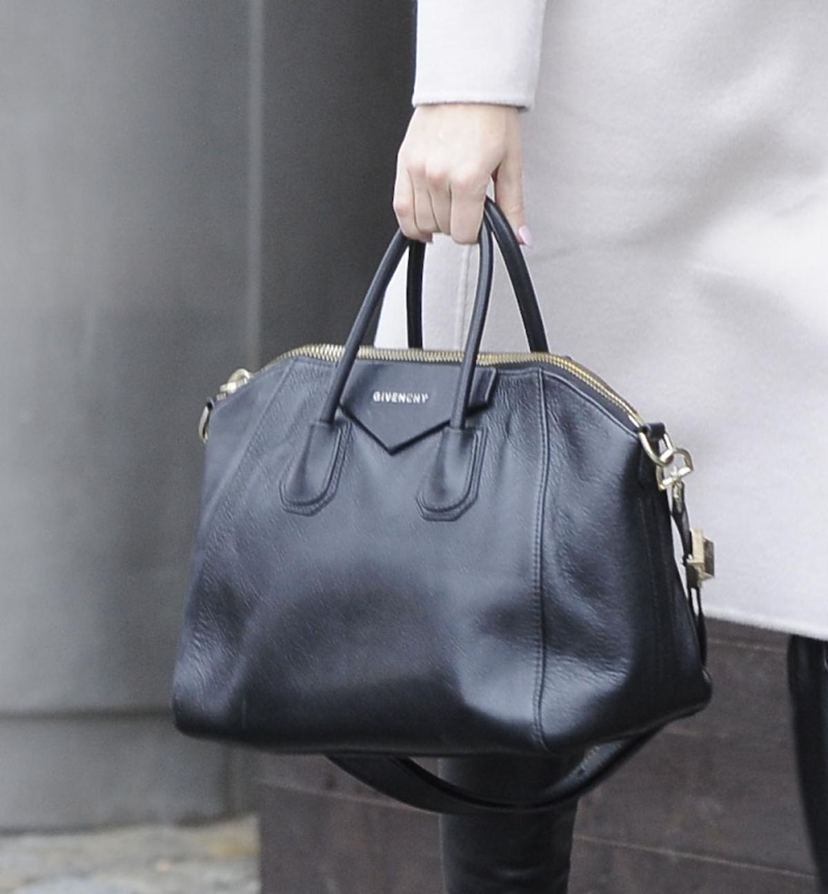 Edyta Herbuś w białym płaszczu z czarną torbą i kozakach