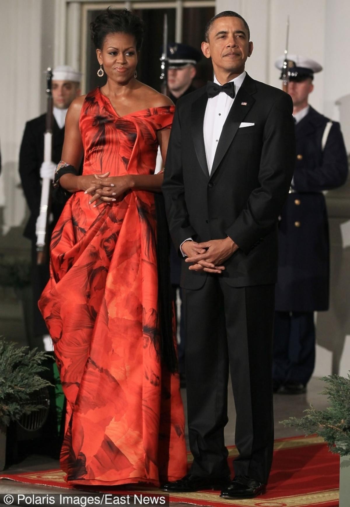 Michelle Obama w czerwonej sukni z czarnymi wzorami , Barack Obama w czarnym smokingu
