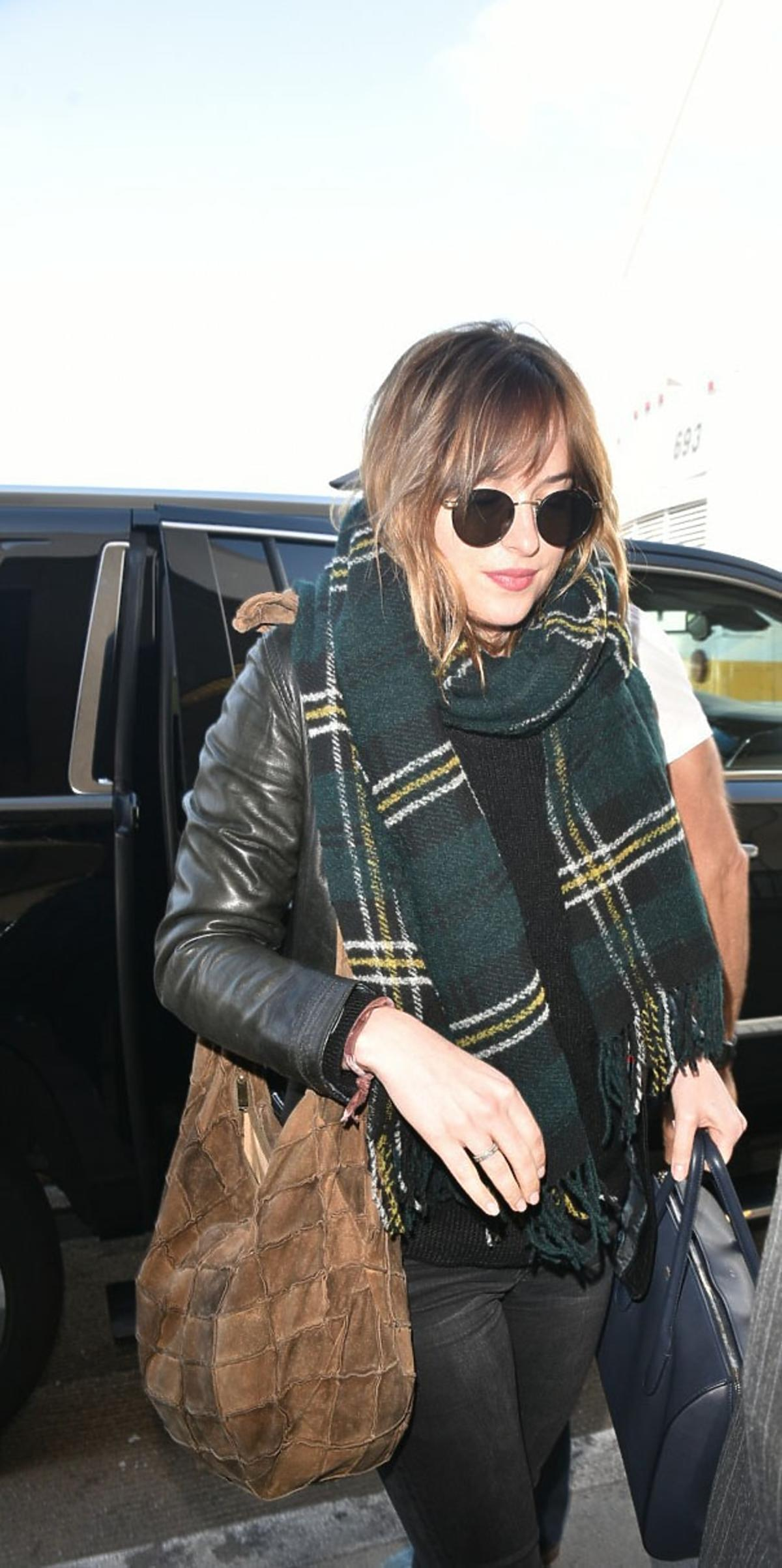 Dakota Johnson w czarnej skórzanej kurtce, szaliku w kratę, brązowątorbą