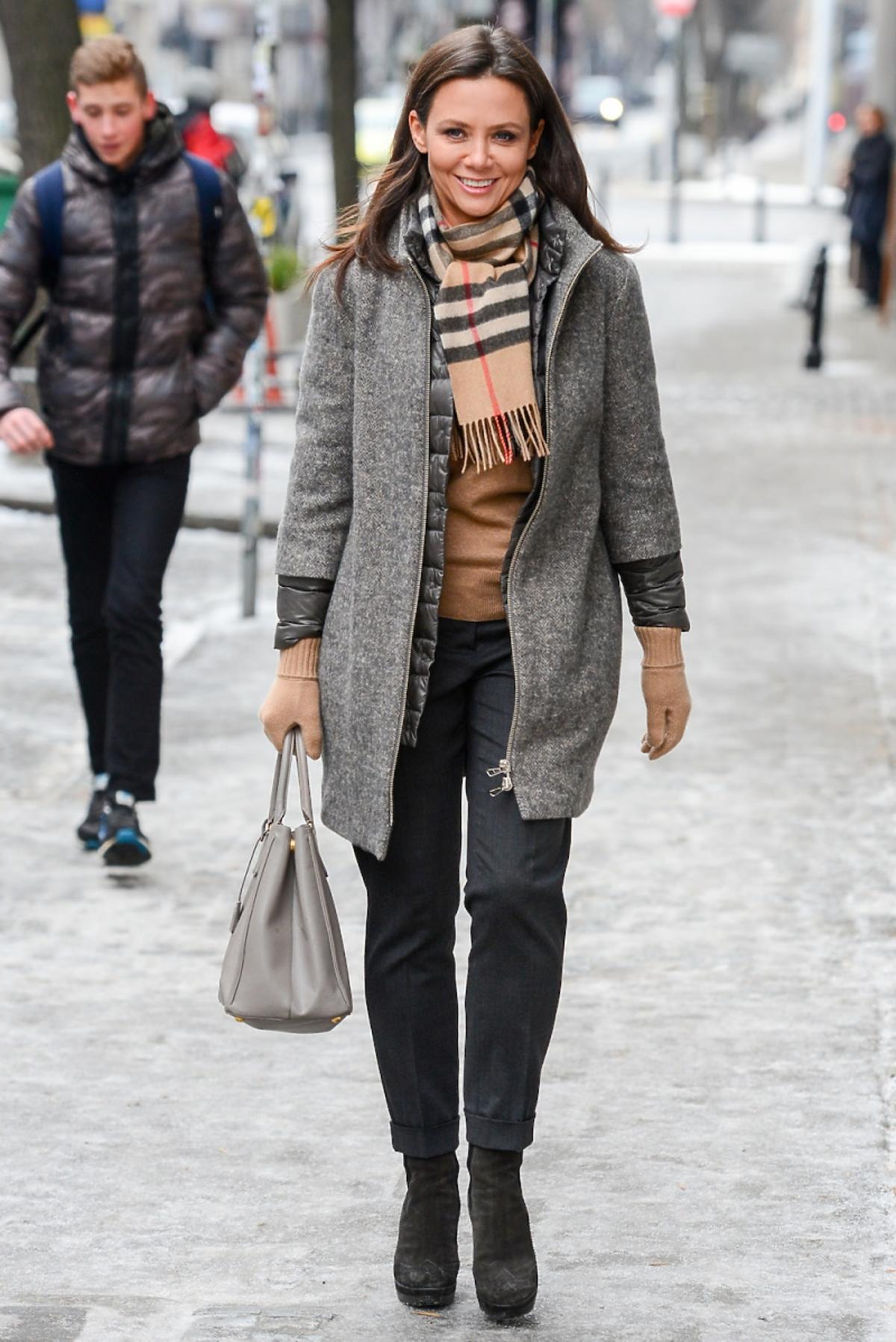 Kinga Rusin w szarym płaszczu, ciemych spodniach, szara torba, szalik w kratę