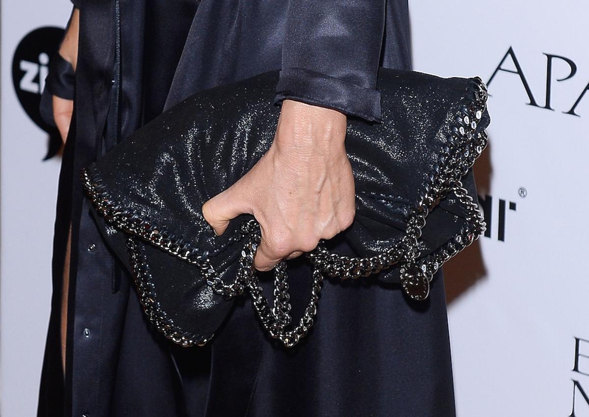 Aneta Kręglicka w czarnej sukni, duża grafitowątorbą ozdobioną srebrnym łańcuszkiem, Czarnych kozakach z odsłoniętymi palcami