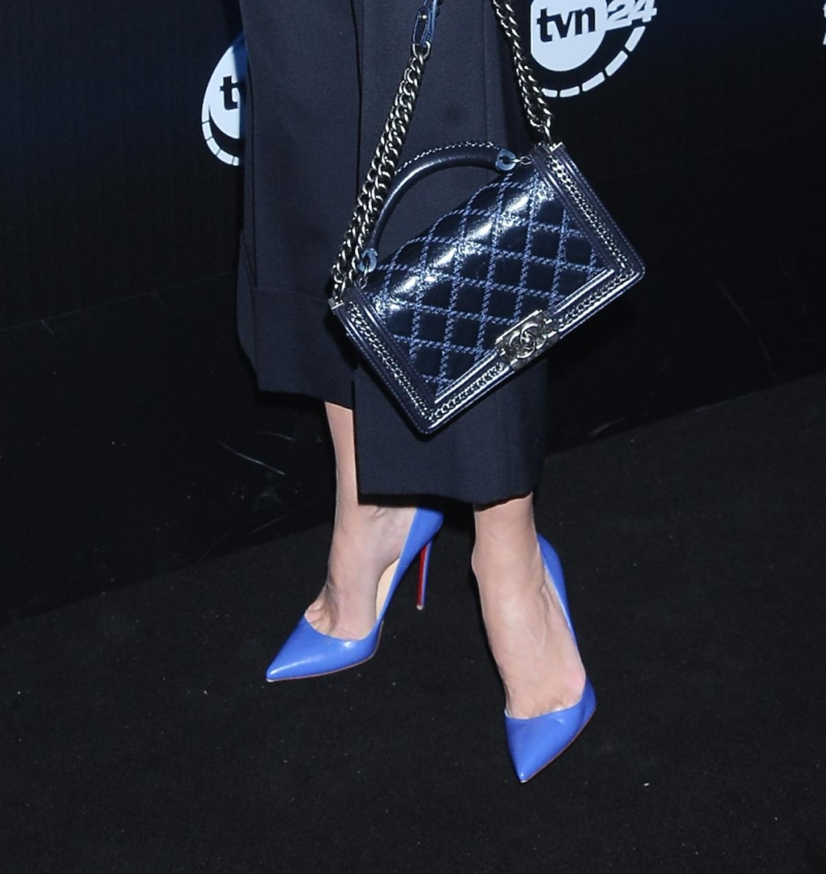 Małgorzata Kożuchowska w czarnych spodniach, niebieskich szpilkach, błyszczącej bluzce różowo-bordowej, grantanową torebką na pasku