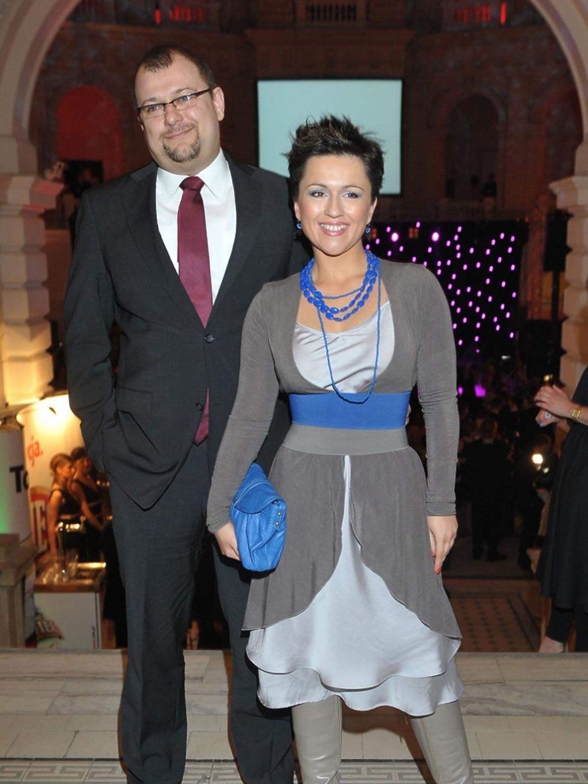 Beata Tadla w szarej sukience z niebieskimi dodatkami pozuje z ówczesnym mężem fotoreporterom podczas Charytatywnego Balu Dziennikarzy w auli Politechniki warszawskiej