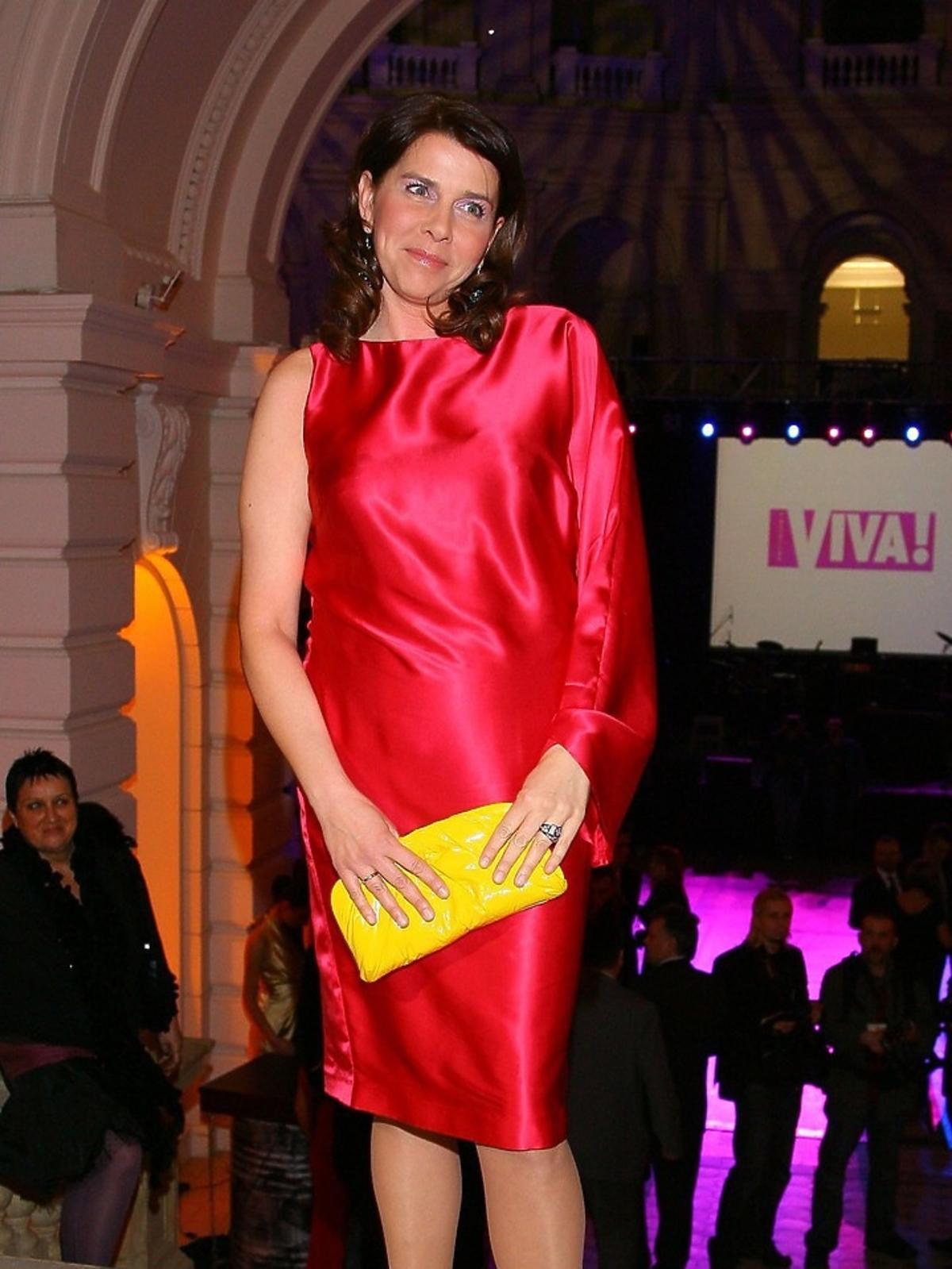 Katarzyna Kolenda-Zaleska w czerwonej sukience z żółtą torebką pozuje fotoreporterom podczas Charytatywnego Balu Dziennikarzy w Auli Politechniki Warszawskiej