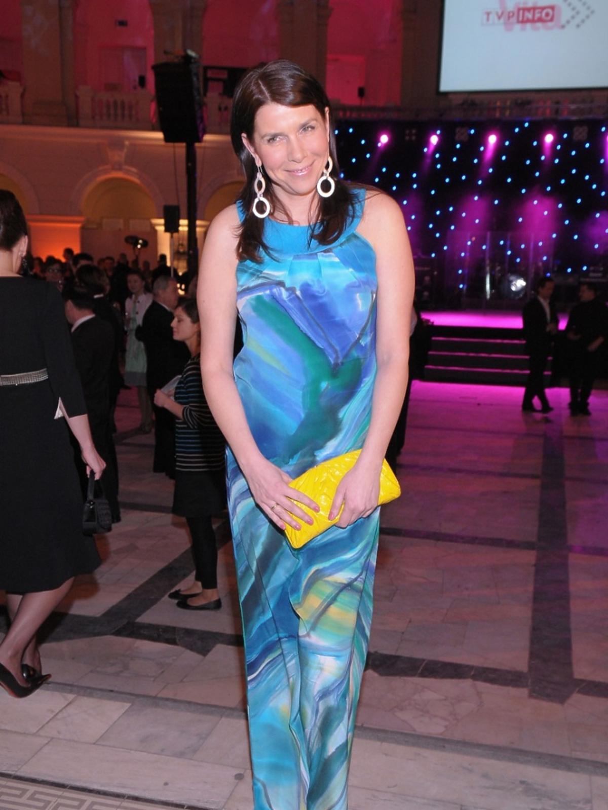 Katarzyna Kolenda-Zaleska w długiej niebieskiej sukience, czarnych butach z żółtą torebka pozuje fotoreporterom podczas Charytatywnego Balu Dziennikarzy w Auli Politechniki Warszawskiej