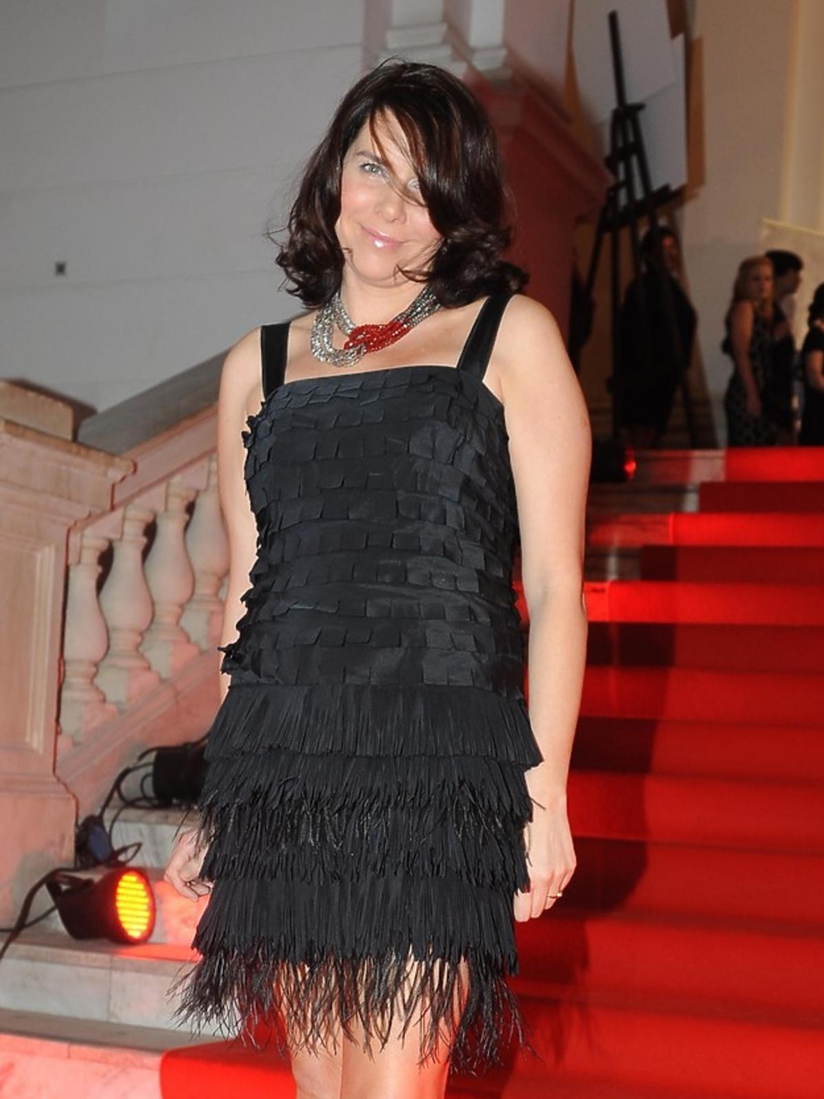 Katarzyna Kolenda-Zaleska w krótkiej, czarnej sukience pozuje na czerwonym dywanie fotoreporterom podczas Charytatywnego Balu Dziennikarzy w Auli Politechniki Warszawskiej