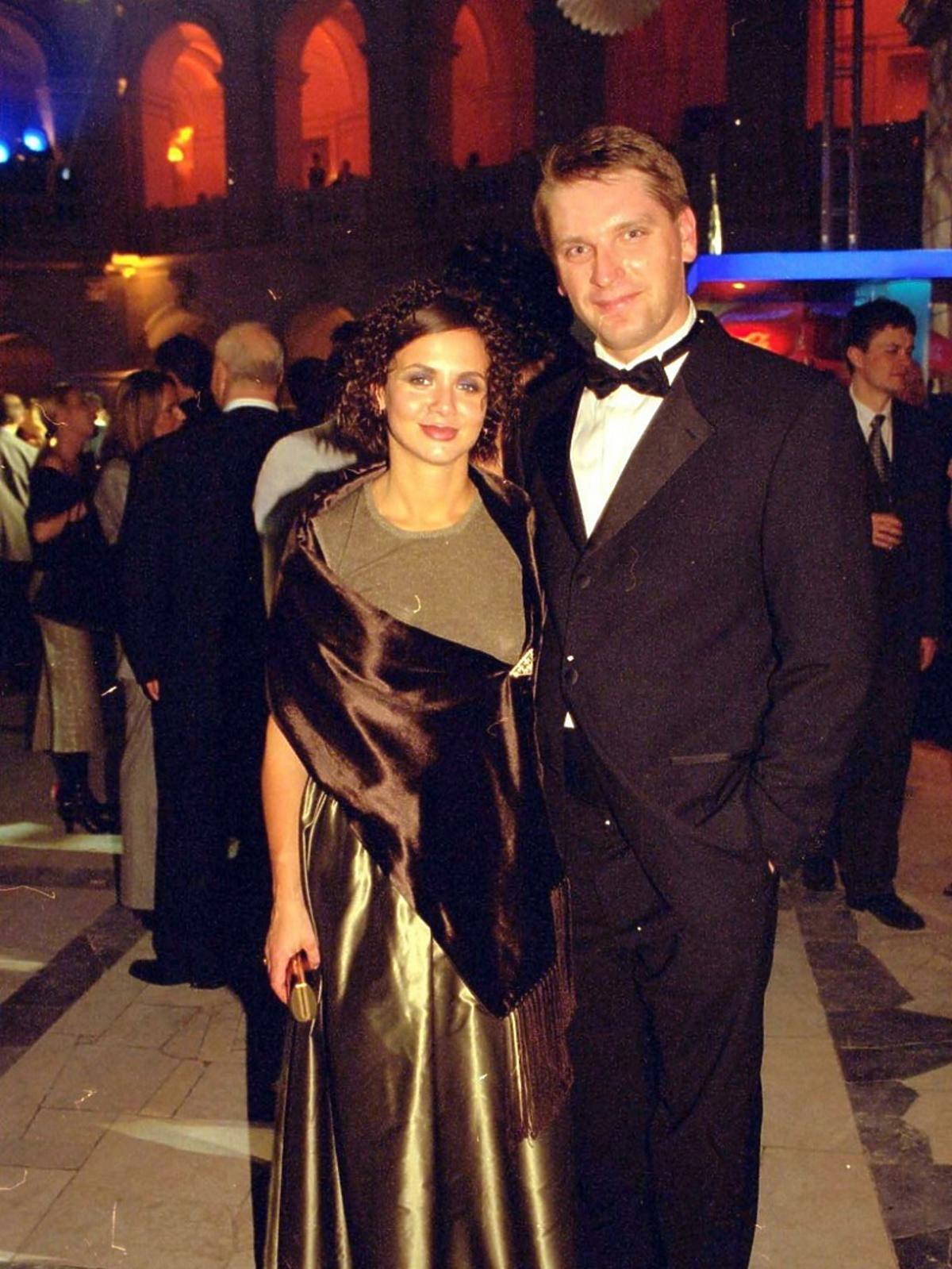 Kinga Rusin w długiej złotej sukni i Tomasz Lis w garniturze na Charytatywnym Balu Dziennikarzy pozują fotoreporterom