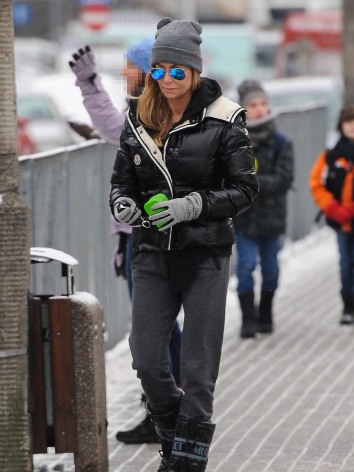 Małgorzata Rozenek w czarnej puchowej kurtce, szarej czapce i spodniach, czarnych butach w niebieskich okularach lustrzankach