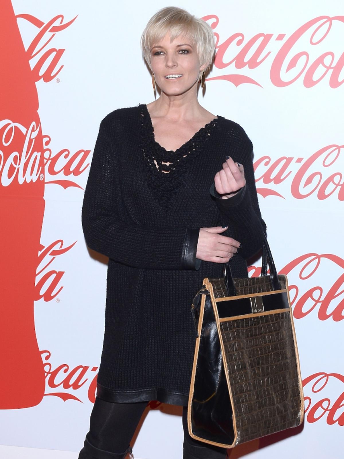 Ilona Felicjańska w czarnej bluzce i spodniach i dużą brązową torbą