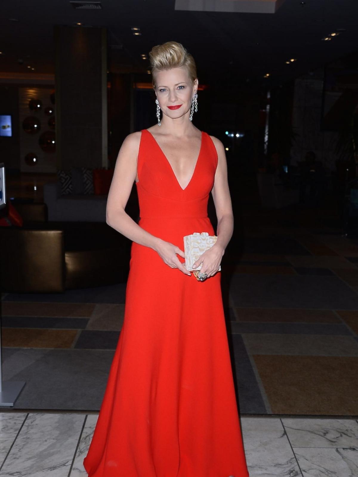 Małgorzata Kożuchowska  w czerwonej sukni z beżową torebką