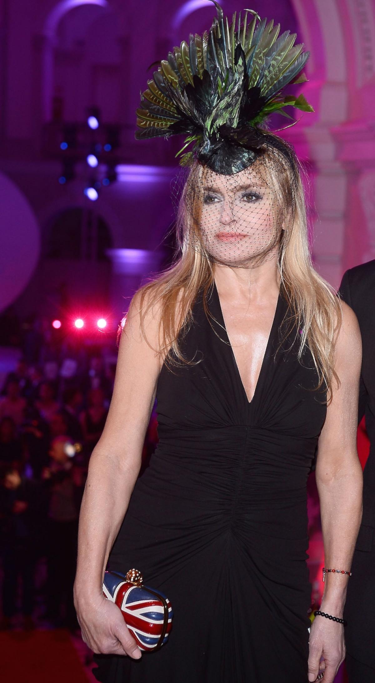 Monika Olejnik w czarnej sukni w kapeluszem w kszatałcie ptaka na głowie