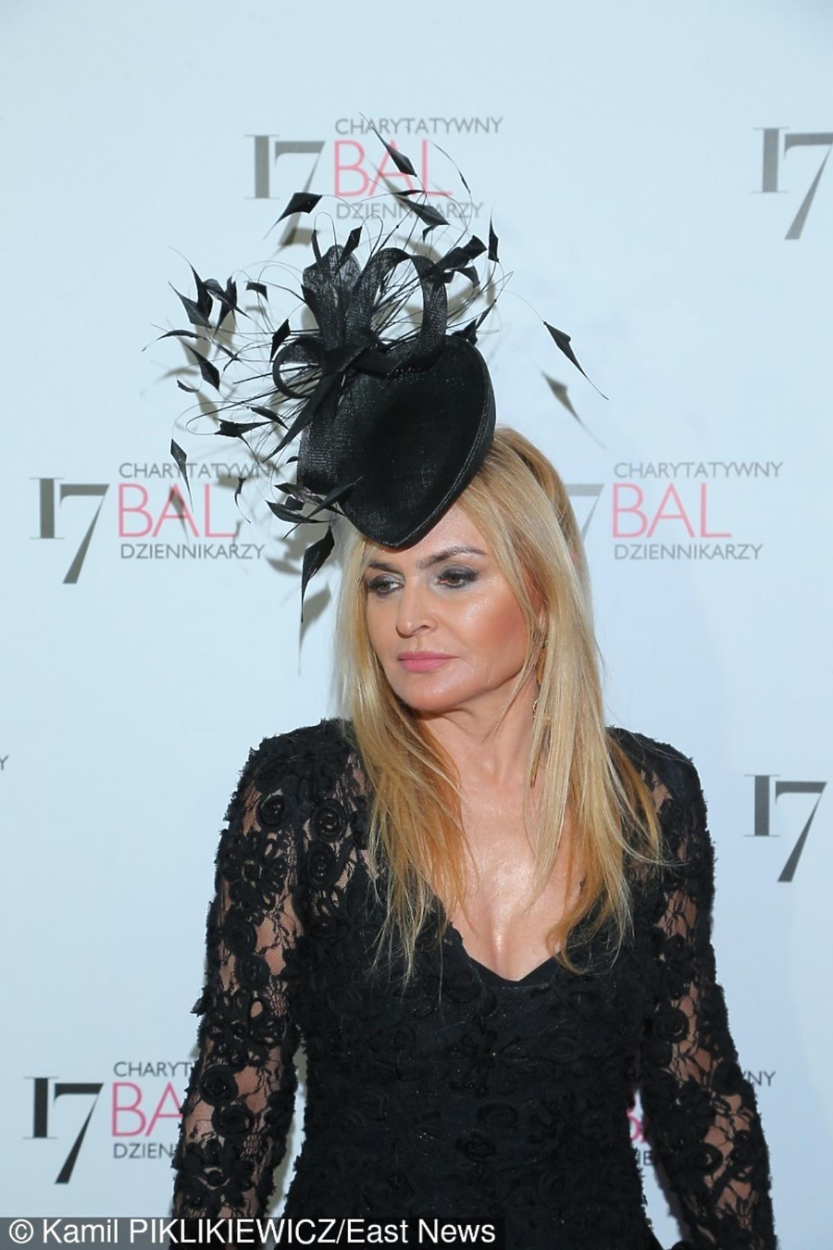 Monika Olejnik w czarnej koronkowej sukni ze stroikime na głowie