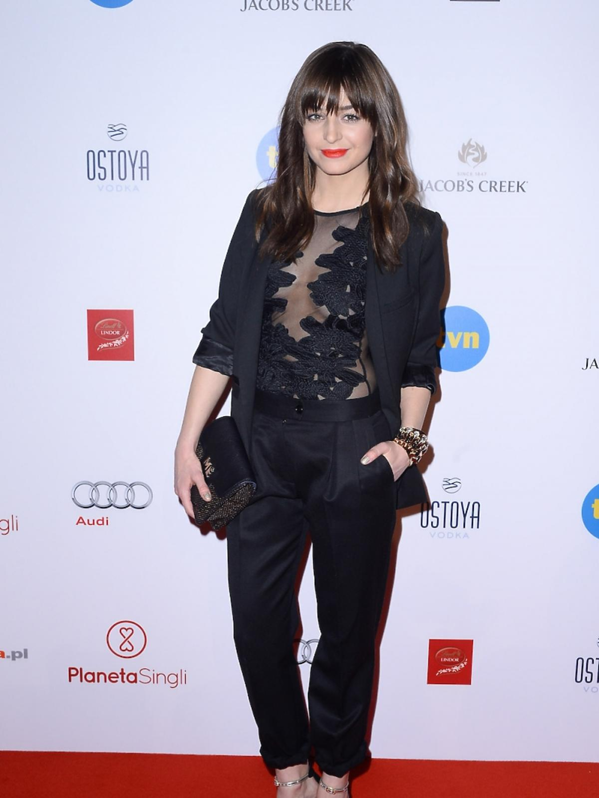 Agnieszka Więdłocha w czarnym garniturze i transparentnej bluzce z wzorem, szpilach z torebką