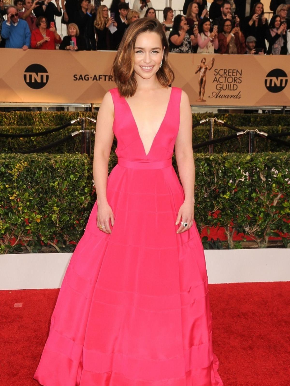 Emilia Clarke w sukni do ziemi w kolorze fuksji na czerwonym dywanie