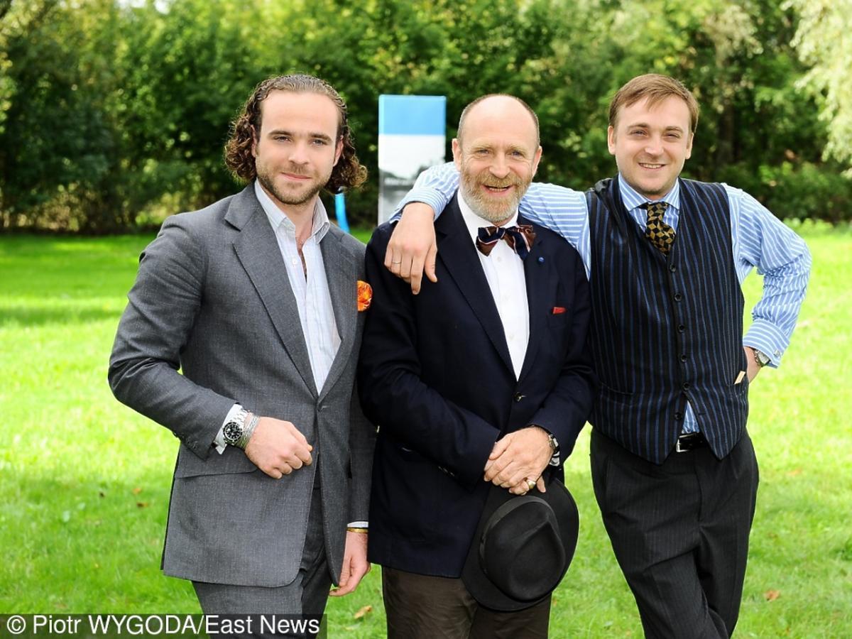 Adam Gessler ojciec z synami Adamem i Mateuszem Gesslerami w garniturach stoją objęci na zielonym trawniku