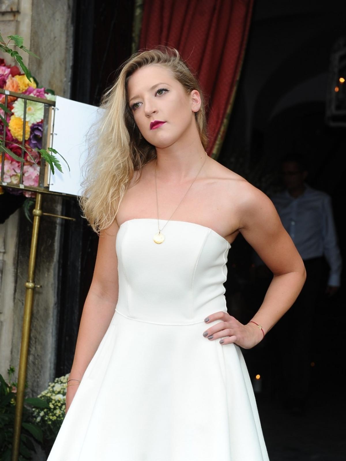 Lara Gessler plan amerykański w białej sukience stoi, ma rozpuszczone włosy