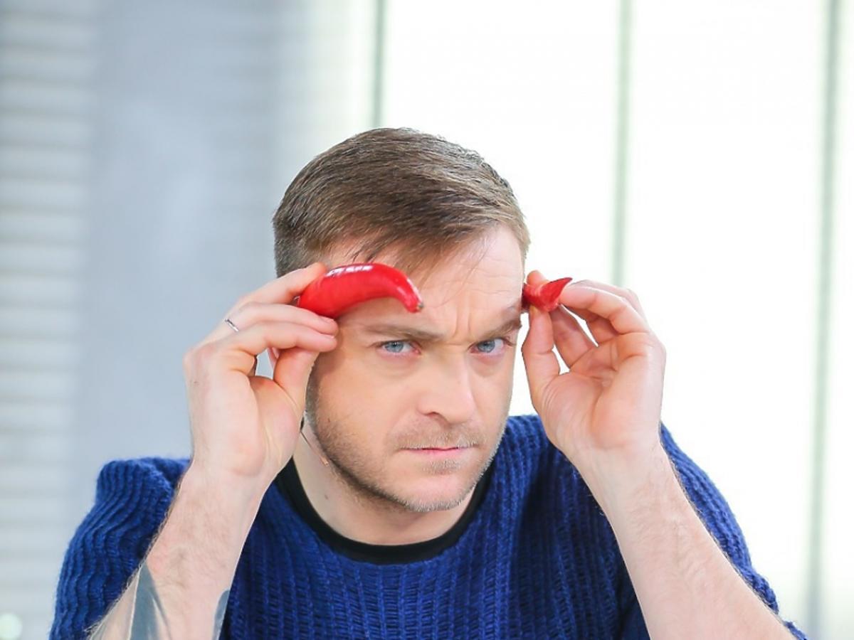 Mateusz Gessler w granatowym sweterku przyprawia sobie rogi z papryki