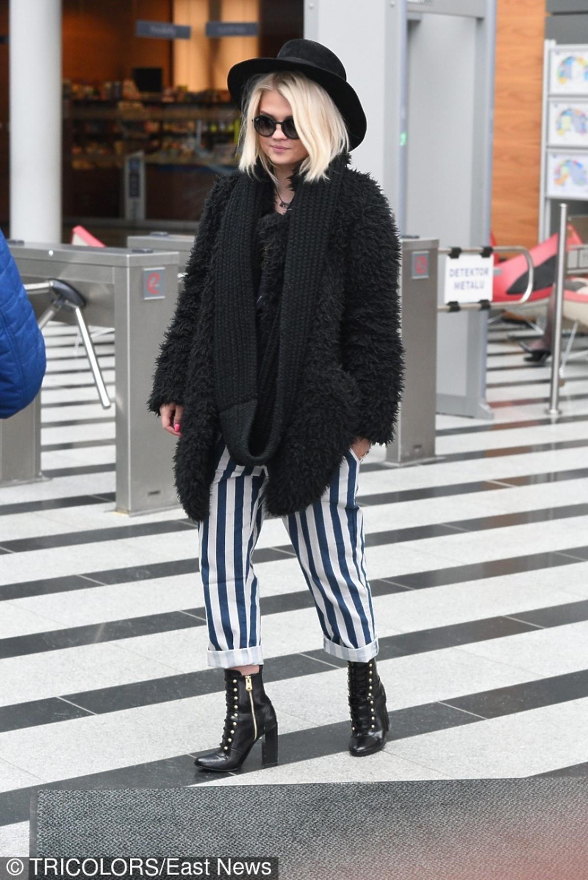 Margaret w spodniach w paski i w czarnym kapeluszu