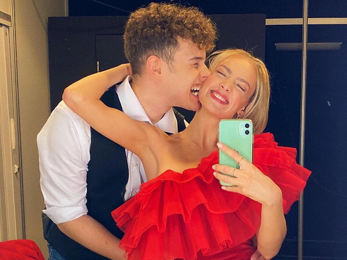 Adam Zdrójkowski całuje Wiktorię Gąsiewską w czerwonej sukience