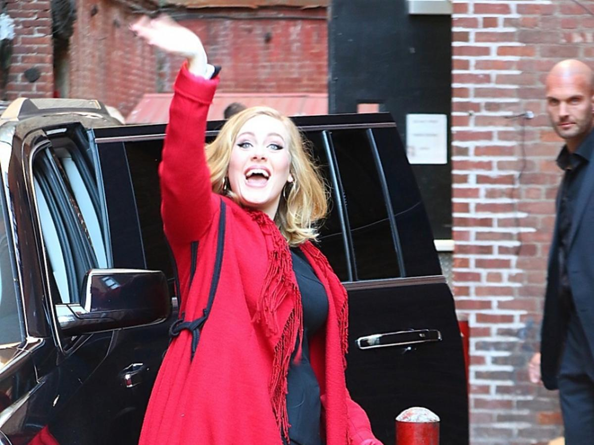 Adele w czerwonym płaszczu macha ręką